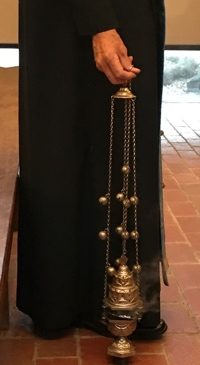 Deacon stands with smoking censer