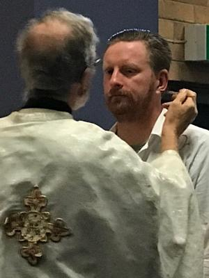 Priest applying the Holy Chrism to a baptismal candidate