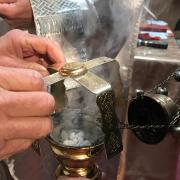 Preparing the censer for incensing.